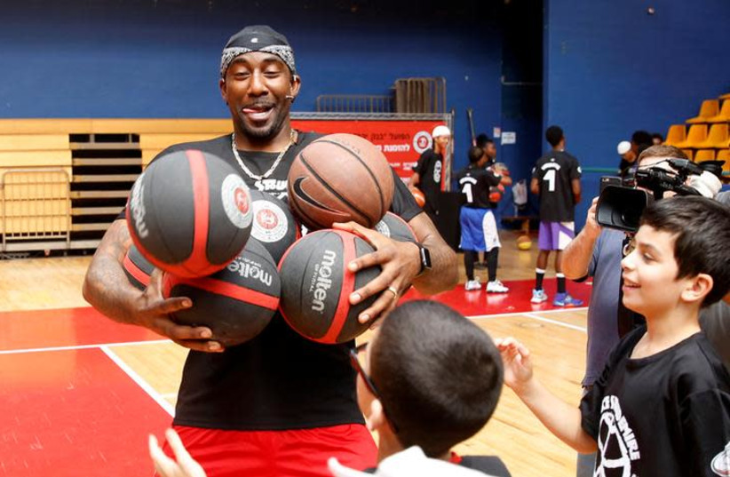 """Former NBA player Amar'e Stoudemire smiles during a basketball workshop for youth entitled """"Amar'e Stoudemire 2016 Basketball Peace Camp"""", August 8, 2016.  (photo credit: RONEN ZVULUN/REUTERS)"""