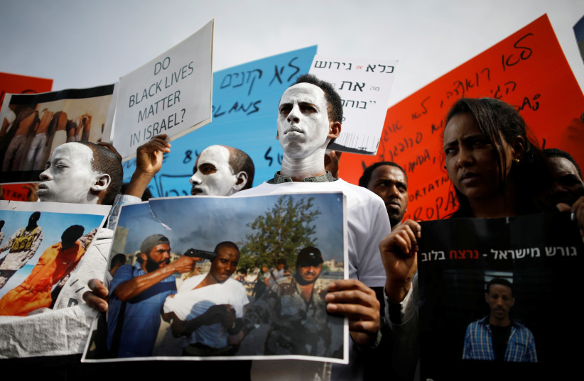 African migrants painted in white hold signs during a protest against the Israeli government's plan to deport part of their community, in front of the Rwandan embassy in Herzliya, Israel (photo credit: AMIR COHEN/REUTERS)