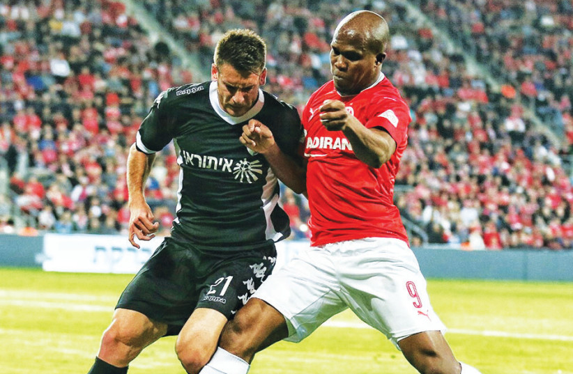 Ironi Kiryat Shmona defender Eyad Abu Abaid (left) battles for the ball with Hapoel Beersheba forward Anthony Nawkaeme (right) during last night's 1-1 draw in the first leg of the State Cup quarterfinals at Turner Stadium. (photo credit: MEIR EVEN HAIM)