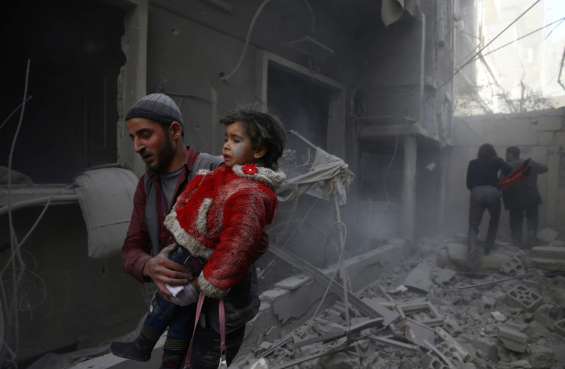 A man holds a child after an airstrike in the besieged town of Douma, Eastern Ghouta, Damascus, Syria February 7, 2018. (photo credit: REUTERS/BASSAM KHABIEH)