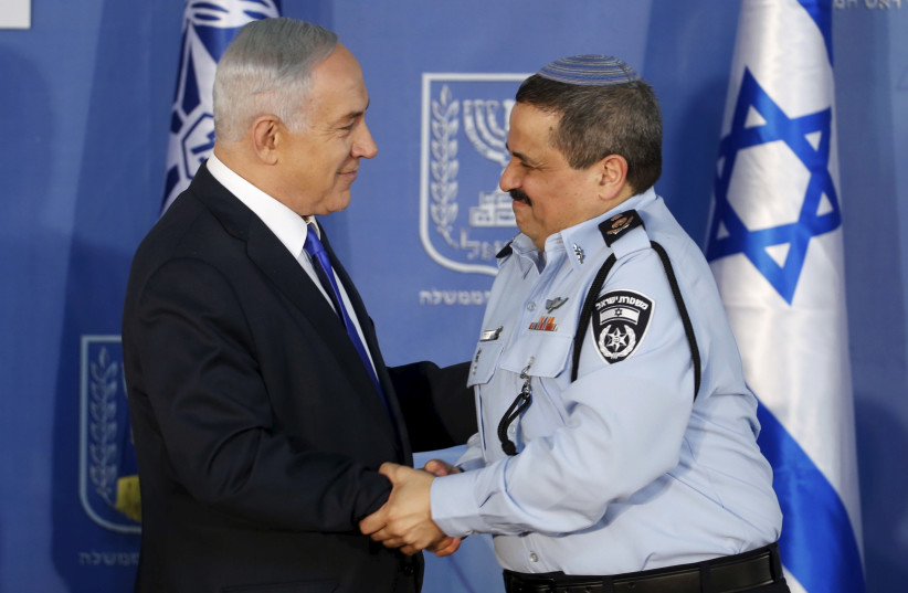Israeli Prime Minister Benjamin Netanyahu (L) congratulates new police commissioner Roni Alsheich after he received his ranks during a ceremony in Jerusalem December 3, 2015. (photo credit: REUTERS)