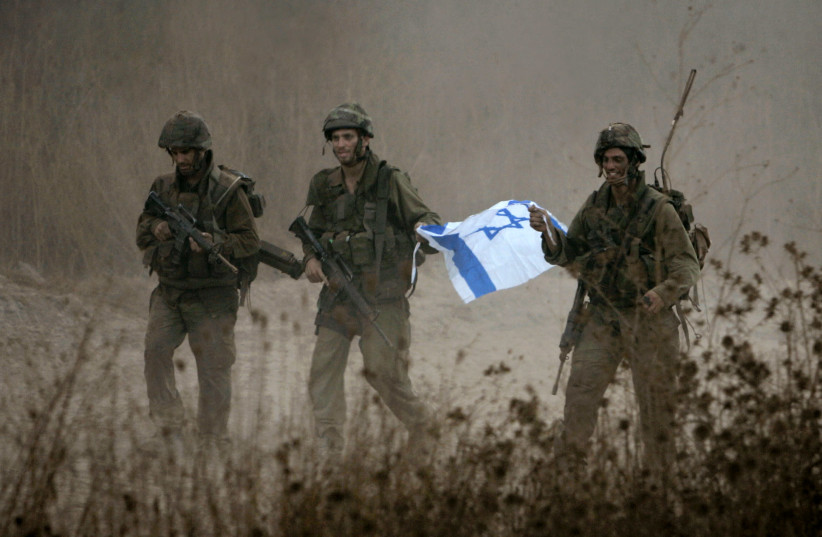 Israeli soldiers hold an Israeli flag as they leave Lebanese territory during a second day of ceasefire during the Second Lebanon War, near the town of Menara August 15, 2006. (photo credit: REUTERS)