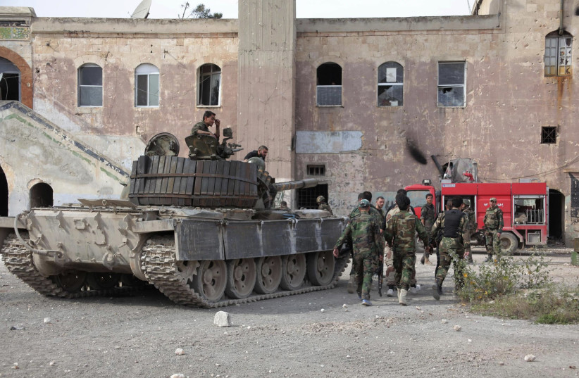A SYRIAN regime tank and soldiers next to a building in central Syria (photo credit: REUTERS)