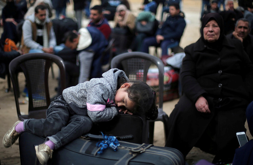 A girl sleeps on a suitcase as she waits with her family for a travel permit to cross into Egypt through the Rafah border crossing (photo credit: IBRAHEEM ABU MUSTAFA / REUTERS)