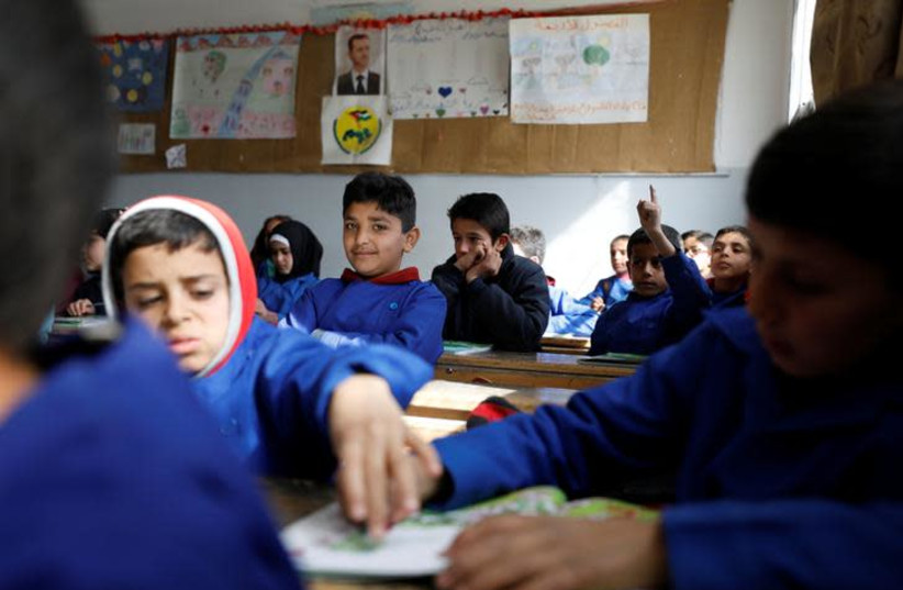 Students sit in a classroom at a school in Sahnaya, near Damascus Syria February 4, 2018. Picture taken February 4, 2018. REUTERS/Omar Sanadiki (photo credit: OMAR SANADIKI/REUTERS)