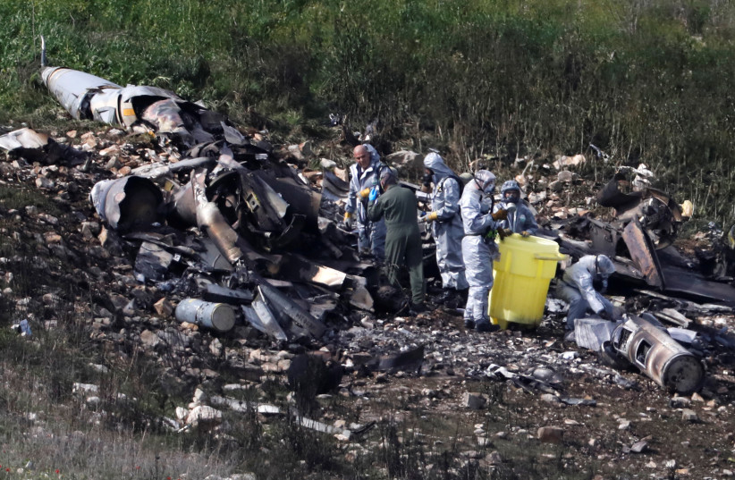 Israeli security forces examine the remains of an F-16 Israeli war plane near the village of Harduf (photo credit: RONEN ZVULUN/REUTERS)