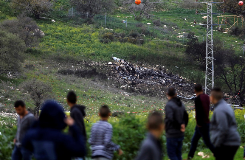 Bystanders look on at the remnants of an Israeli F-16 fighter jet shot down by Syrian forces, February 2018 (photo credit: RONEN ZVULUN/ REURERS)