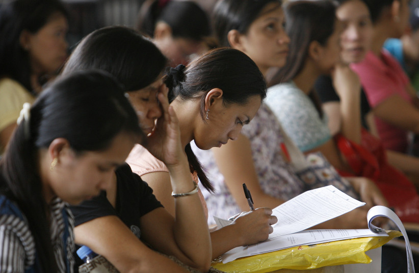 A woman fills an application form for a job posting in Kuwait during a job fair at the Philippine Overseas Employment Agency in Manila in this September 20, 2010 file photo. (photo credit: REUTERS/CHERYL RAVELO/FILES)