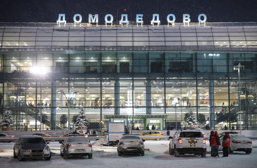Emergency personel stand outside Domodedovo International Airport on February 11, 2018. A Russian passenger plane carrying 71 people crashed outside Moscow after taking off from the capital's Domodedovo airport (photo credit: MAXIM ZMEYEV/REUTERS)