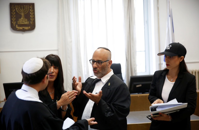 Yehuda Fried (C), lawyer of Malka Leifer, speaks to a state prosecutor (L) after a court session at the Jerusalem District Court (photo credit: RONEN ZVULUN / REUTERS)