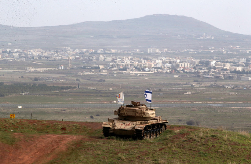 An old military vehicle can be seen positioned on the Israeli side of the border with Syria, near the Druze village of Majdal Shams in the Golan Heights (photo credit: AMMAR AWAD/REUTERS)