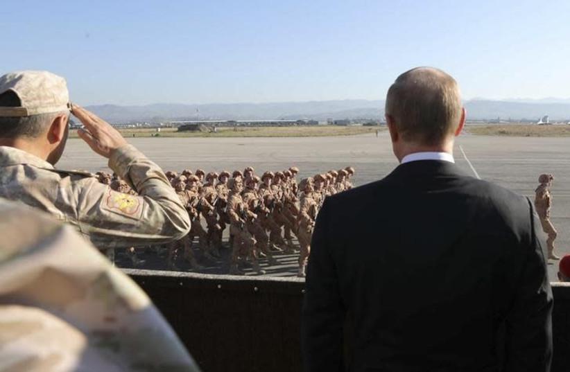 Russian President Vladimir Putin (R) and Defence Minister Sergei Shoigu watch servicemen passing by as they visit the Hmeymim air base in Latakia Province, Syria December 11, 2017 (photo credit: SPUTNIK/MIKHAIL KLIMENTYEV/KREMLIN VIA REUTERS)