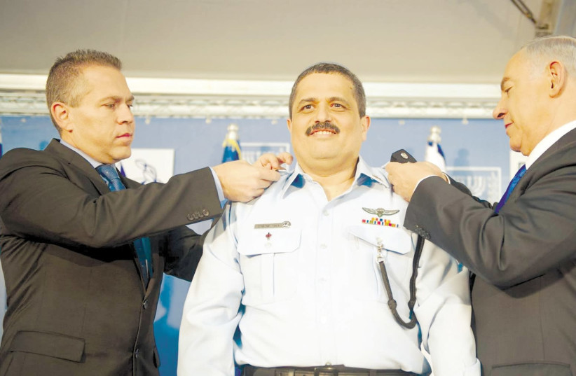 Prime Minister Benjamin Netanyahu pins the rank of police commissioner on Roni Alsheich with help from Public Security Minister Gilad Erdan in December 2015 (photo credit: COURTESY ISRAEL POLICE)