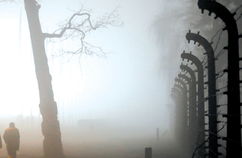 THE PERIMETER fence of Auschwitz II-Birkenau is enveloped in a thick evening fog during the ceremonies marking the 73rd anniversary of the liberation of the camp and International Holocaust Remembrance Day, near Oswiecim, Poland, January 2018 (photo credit: KACPER PEMPEL/REUTERS)