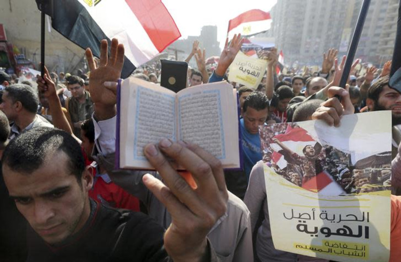 A supporter of the Muslim Brotherhood and ousted Egyptian President Mohamed Mursi holds a copy of the Koran as others shout slogans against the military and the interior ministry during a protest in the Cairo suburb of Matariya November 28, 2014. (photo credit: MOHAMED ABD EL GHANY/REUTERS)
