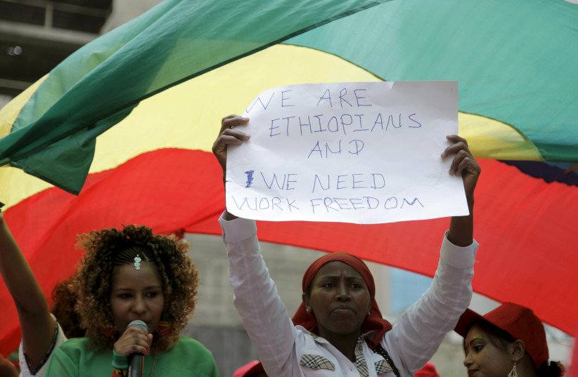 An Ethiopian migrant domestic worker holds up a placard during a parade in Beirut, to support the rights of migrant domestic workers in Lebanon and calling for a domestic workers union in Beirut (photo credit: ALIA HAJU/REUTERS)