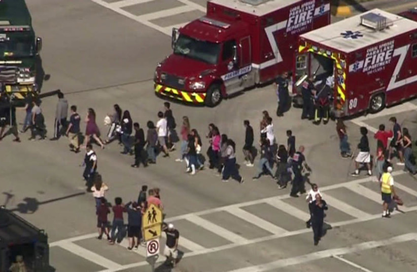 Students are evacuated from Marjory Stoneman Douglas High School during a shooting incident in Parkland, Florida, February 14  (photo credit: WSVN.COM VIA REUTERS)