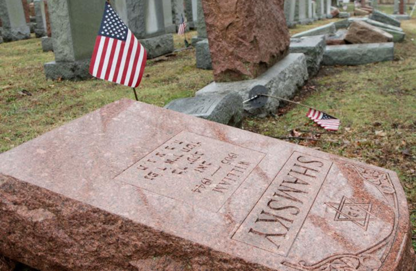 An American flag still stands next to one of over 170 toppled Jewish headstones after a weekend vandalism attack on Chesed Shel Emeth Cemetery in University City, a suburb of St Louis, Missouri, U.S. February 21, 2017. (photo credit: REUTERS/TOM GANNAM)