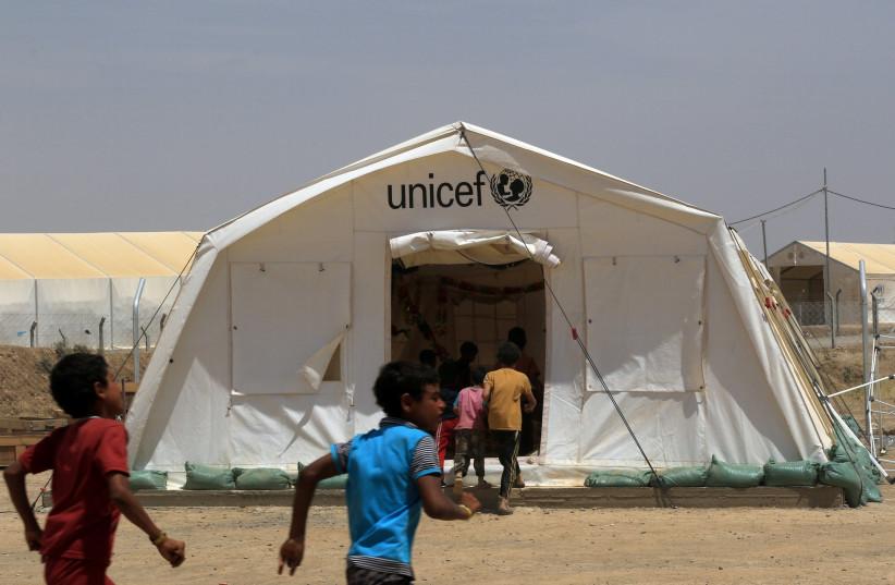 Displaced Iraqi boys enter a tent school set by United Nations Children's Fund (UNICEF) at Hammam al-Alil camp south of Mosul, Iraq (photo credit: ARI JALAL / REUTERS)