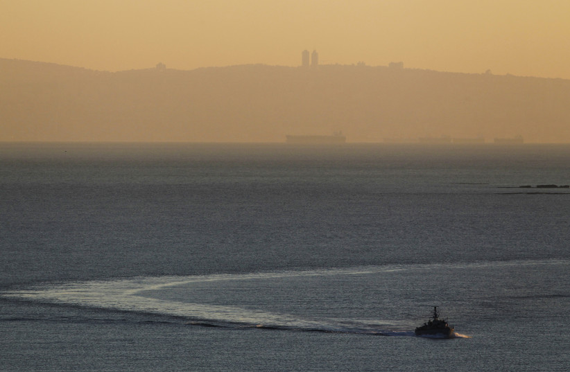 An Israeli naval vessel sails in the Mediterranean sea near the border with Lebanon, as Mount Carmel and the Israeli city of Haifa are seen in the background December 16, 2013 (photo credit: REUTERS/AMIR COHEN)