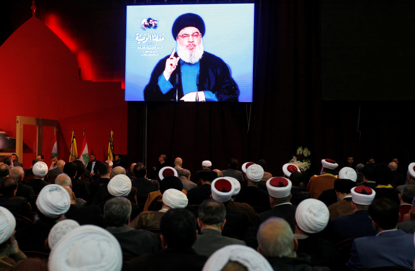 Lebanon's Hezbollah leader Sayyed Hassan Nasrallah is seen on a video screen as he addresses his supporters in Beirut, Lebanon February 16, 2018. (photo credit: REUTERS)