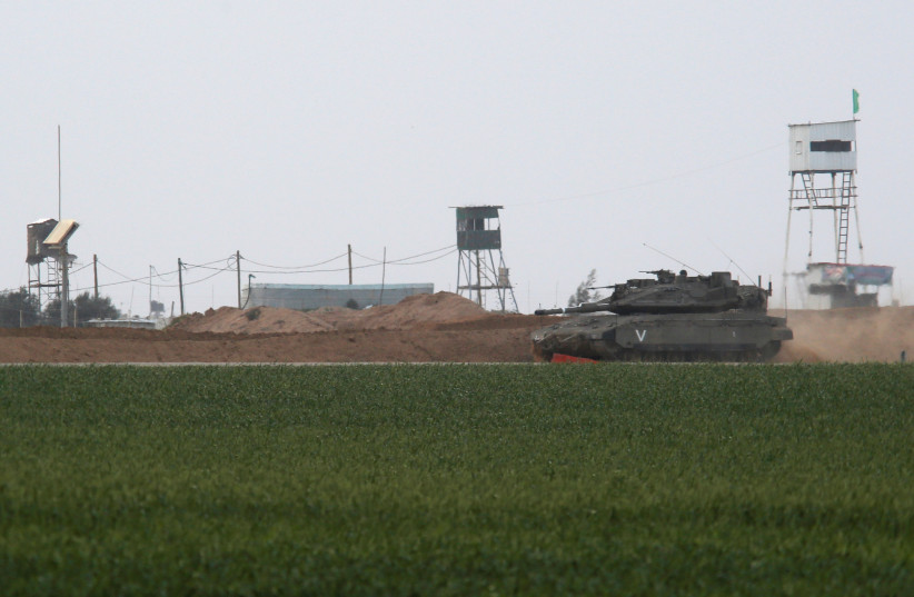 An Israeli tank manoeuvres along the border fence with the southern Gaza Strip, as watch-towers are seen on the Palestinian side near Kibbutz Nirim, Israel February 17, 2018 (photo credit: REUTERS/AMIR COHEN)
