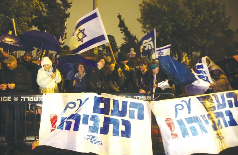 "Protesters holding signs that say ""The nation is with Netanyahu"".  (photo credit: MARC ISRAEL SELLEM/THE JERUSALEM POST)"