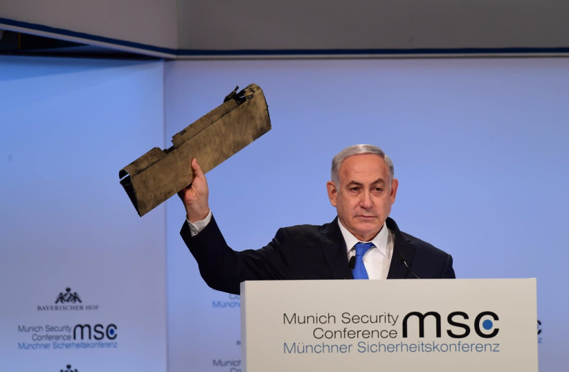 Prime Minister Benjamin Netanyahu holds up part of Iranian drone that landed in Israel in February 2018 at the Munich Security Conference, February 18, 2018 (photo credit: AMOS BEN-GERSHOM/GPO)