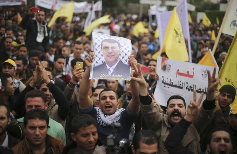 A Palestinian supporter of former head of Fatah in Gaza, Mohammed Dahlan, holds a poster depicting Dahlan during a protest against Palestinian President Mahmoud Abbas in Gaza City December 18, 2014 (photo credit: MOHAMMED SALEM/REUTERS)