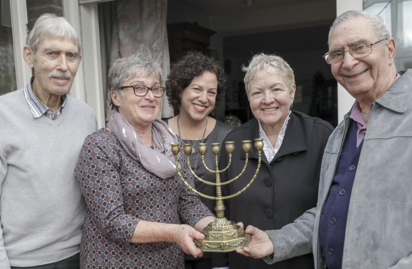 From left to right: Hubert Baumeister, Roswitha Baumeister, Yotvat Palter Dycian, Aviva Palter, Guri Palter hold the menorah at the home of Hubert and Roswitha Baumeister in Osnabrück on February 5th (photo credit: JÖRN MARTENS)