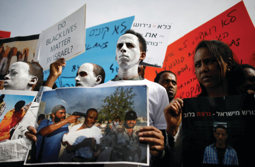 African migrants painted in white hold signs during a protest against the Israeli government's plan to deport part of their community, in front of the Rwandan embassy in Herzliya, Israel February 7, 2018 (photo credit: AMIR COHEN/REUTERS)