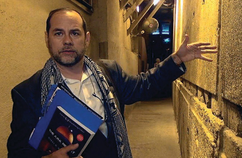 Harry Moskoff, holding his book, tours the Western Wall tunnels (photo credit: HARRY MOSKOFF)