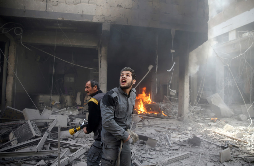 A civil defense member reacts at a damaged site after an airstrike in the besieged town of Douma, Eastern Ghouta, Damascus, Syria (photo credit: REUTERS/BASSAM KHABIEH)