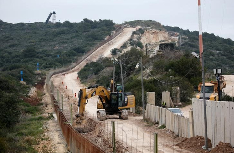 Israeli workers are seen building a wall near the border with Israel near the village of Naqoura, Lebanon February 8, 2018 (photo credit: REUTERS/ALI HASHISHO)