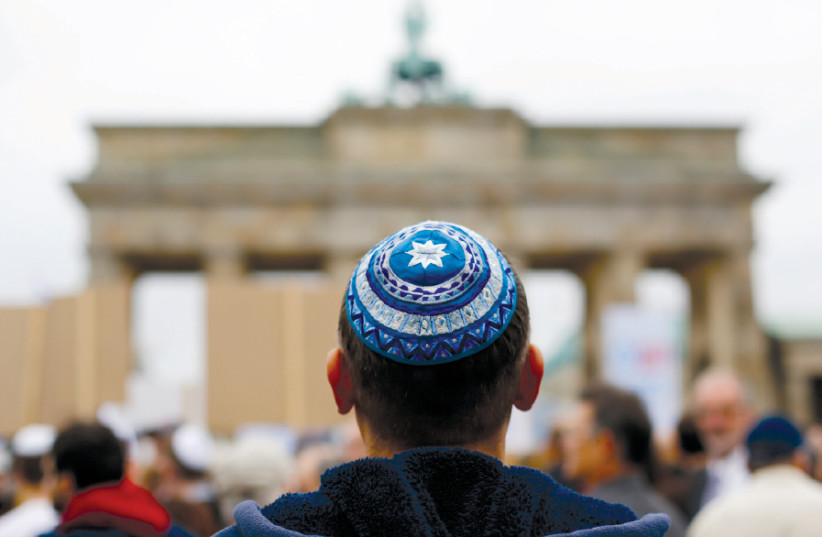 A MAN wearing a kippa waits for the start of a demonstration against antisemitism at Berlin's Brandenburg Gate in 2014 (photo credit: THOMAS PETER/REUTERS)