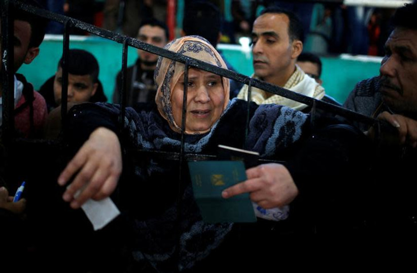 A woman waits for a travel permit to cross into Egypt through the Rafah border crossing after it was opened by Egyptian authorities for humanitarian cases, in the southern Gaza Strip February 21, 2018. REUTERS/Mohammed Salem (photo credit: REUTERS/MOHAMMED SALEM)