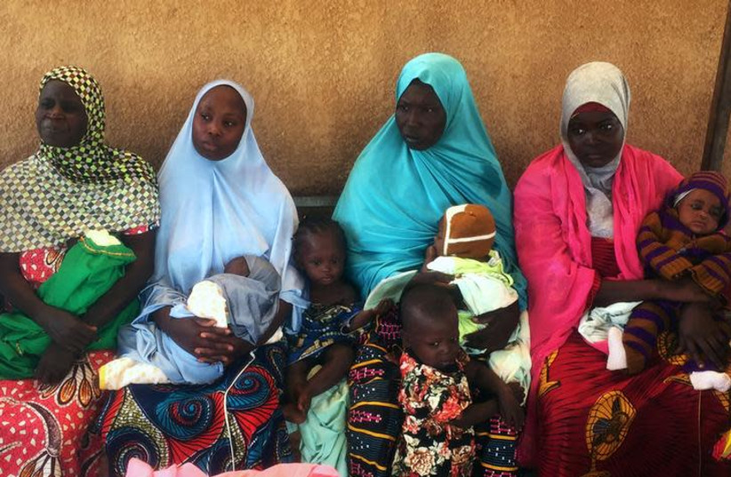 Women carry children as they wait to see a nurse at a pop-up Marie Stopes clinic in Niger's village of Libore (photo credit: REUTERS/TIM COCKS)