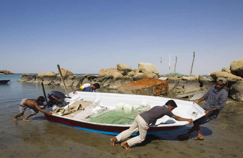 Local Baluch fishermen push a boat to the shore at a fishing port in Tiss village in the suburb of the port city of Chabahar 1,452 km (902 miles) southeast of Tehran, near Strait of Hormuz January 16, 2012. (photo credit: REUTERS/RAHEB HOMAVANDI)