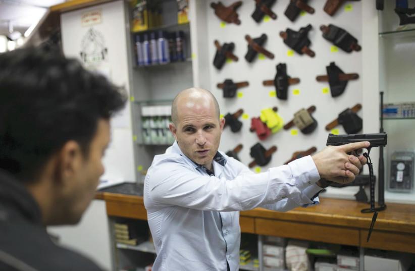 A SALESMAN shows a pistol to a customer at a gun shop in Tel Aviv. (photo credit: REUTERS/BAZ RATNER)