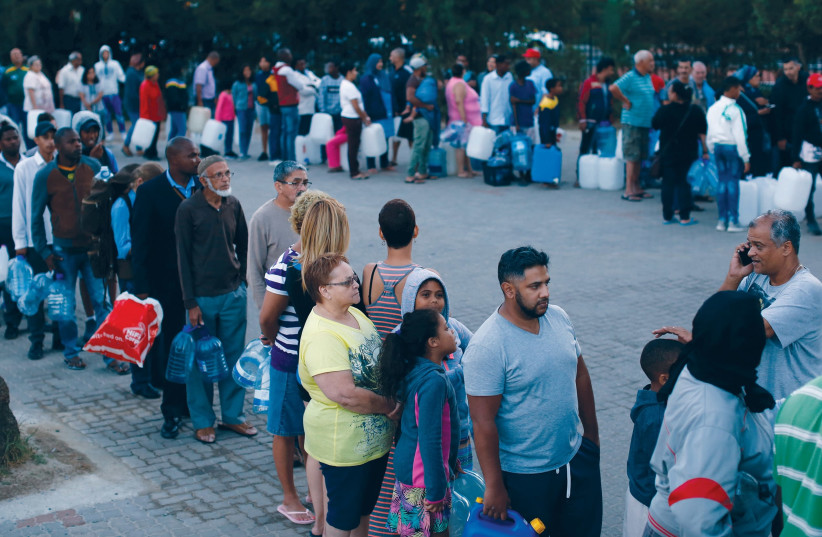PEOPLE WAIT to collect water from a spring last month in the Newlands suburb of Cape Town as fears grow over the South African city's water crisis. (Mike Hutchings/Reuters) (photo credit: REUTERS/MIKE HUTCHINGS)