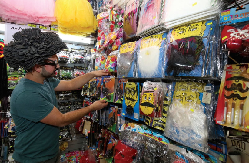 A CUSTOMER tries on a disguise and looks at costumes in a Jerusalem shop this week. (Marc Israel Sellem/The Jerusalem Post) (photo credit: MARC ISRAEL SELLEM/THE JERUSALEM POST)