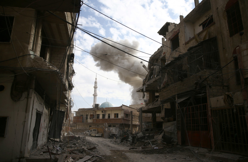 Smoke rises from the rebel held besieged town of Hamouriyeh, eastern Ghouta, near Damascus, Syria, February 21, 2018 (photo credit: REUTERS/BASSAM KHABIEH)