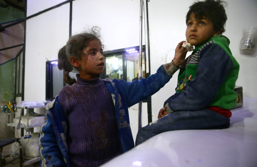 Wounded children are seen in a hospital in the besieged town of Douma, Eastern Ghouta, Damascus, Syria February 23, 2018.  (photo credit: REUTERS/BASSAM KHABIEH)
