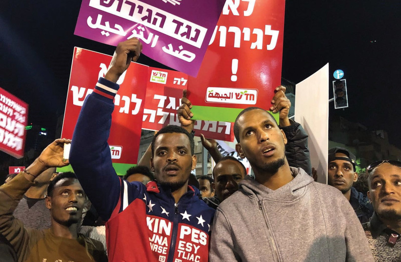 AFRICAN ASYLUM-SEEKERS hold signs during a protest against the Israeli government's plan to deport part of their community. (photo credit: ANNA AHRONHEIM)