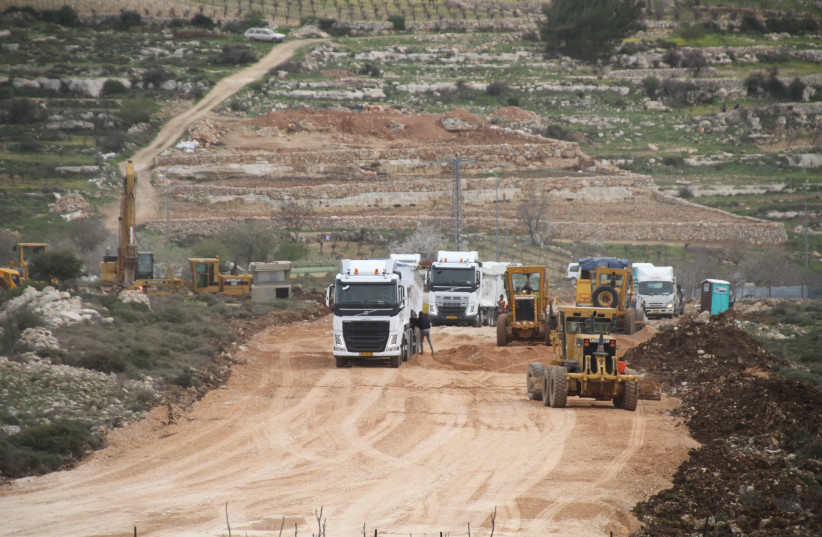 Trucks and cranes building a new road for Civil Administration vehicles to access the outpost during the demolition of 15 homes. (photo credit: TOVAH LAZAROFF)