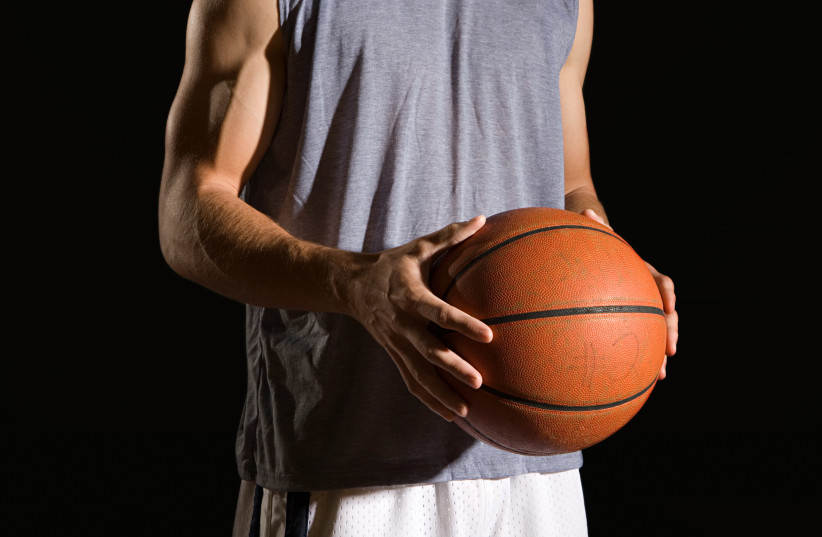 Man holding a basketball (photo credit: INGIMAGE)