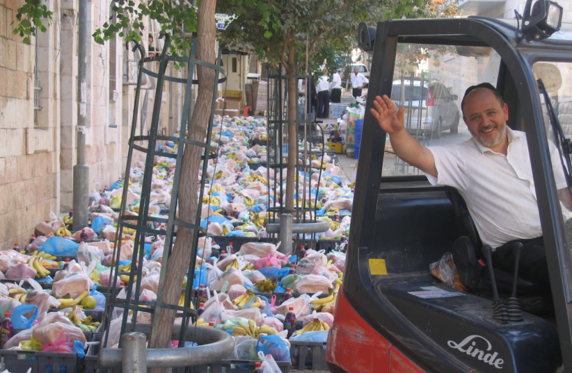 Yad Ezra V'shulamit CEO Benny Lurie operated a forklift loaded with donations (photo credit: YAD EZRA VESHULAMIT)
