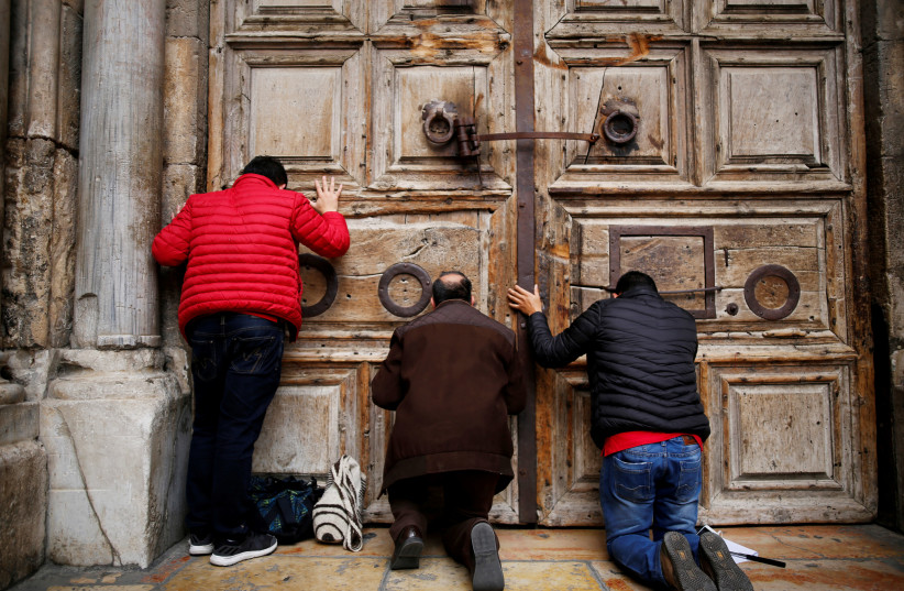 Worshippers kneel and pray in front of the closed doors of the Church of the Holy Sepulchre in Jerusalem's Old City (photo credit: AMIR COHEN/REUTERS)
