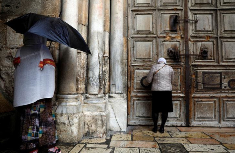 Worshippers stand in front of the closed doors of the Church of the Holy Sepulchre in Jerusalem's Old City February 26, 2018. REUTERS/Ronen Zvulun (photo credit: REUTERS/Ronen Zvulun)