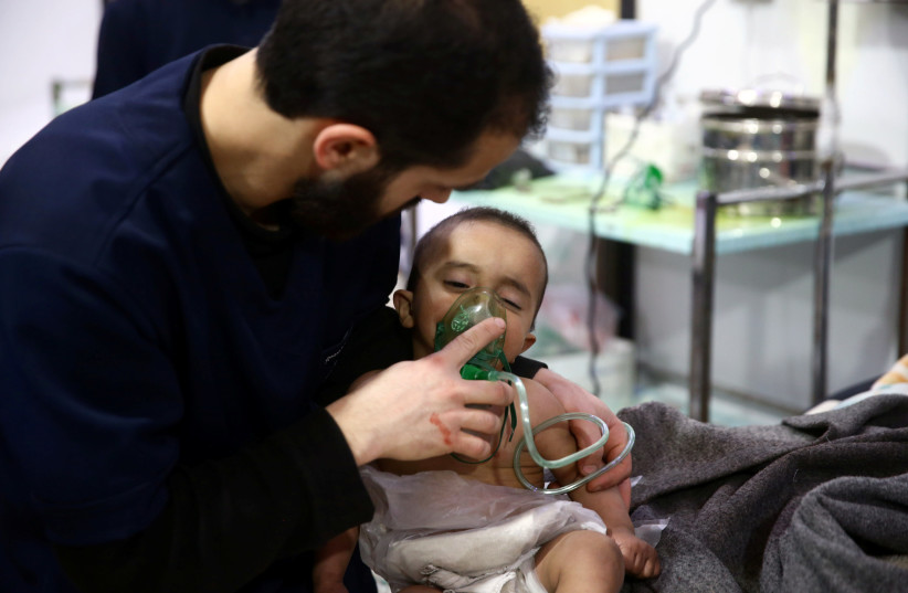Man with a child in a hospital in the besieged town of Douma, Eastern Ghouta, Damascus, Syria (photo credit: REUTERS/BASSAM KHABIEH)